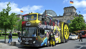 Open top doubledecker fan coach in front of The Reichstag Building